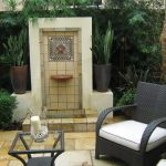 mini patio with a couple of patio furniture set and simple water feature corner old-look flooring for patio