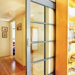modern glass barn sliding door with white-colored frame