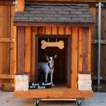 movable dog house with hanging bone accessory on top of door