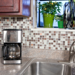 multiple color groutless tiles for kitchen backsplash  a machine coffee maker unit mini garden window in kitchen a stainless steel kitchen sink  and stainless steel faucet grey granite finishing counterntop