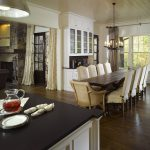 narrow but long dining table made from wood with white rattan seaters ancient chandelier in black a kitchen island with black-finished top pendant lamp for kitchen area dishware items wood laminate floor