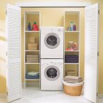 opened-door laundry room cabinet for washing and drying machine unit which is associated with linens laundry supplies organizers a dried-roots basket for storing clean laundries small white tiles floor