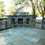 outdoor kitchen set with natural stones floor which look like paver