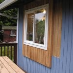outside window trim in white color with wood planks surround it