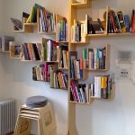 Plenty Of Books Organized In Tree Shaped Bookcase A Pile Of Plastic Chairs