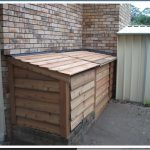 pool equipment enclosure in the corner which made from wood material