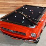pool table with unique car shape in red and black as the surface for playing billiard