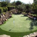 putting green golf with white flags surrounded by natural stones fence system