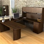 rustic  U shaped desk with cabinets and drawers features a computer sets a pile of books clear-lines wood flooring bricks wall system