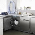 silver color cabinet system for laundry machine  large garden windows with small pots and plant ornaments some rolls of clean white towels a hanging cloth