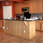 simple remodel of kitchen set with wood material wood kitchen cabinetry solid wood flooring kitchen island with black laminated-vinyl top