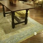 soft green jaunty rug with patterns  a large console table with three pots and vivid plant decorations a round green and back-less chair  dark-brown wood planks flooring