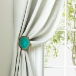 tied-back curtain with blue pin white window curtain