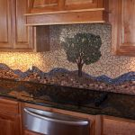 two comined style backsplash tiling between mosaic tiles and river rocks tiles  a-tree-picture backsplash decoration made from mosaic tiles an electric stove as the most modern kitchen appliance