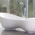 Uniqe Style Bathtub With High Stainless Steel Water Tap In White Tone Luxurious And Expensive Granite Floor A Leather Lazy Chair Frameless Large Glass Windows