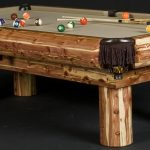 unique pool table made from log wood some billiard balls  and two stick billiard