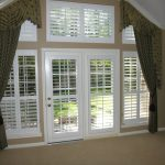 very large French door with shutters and beautiful drapes