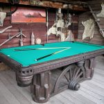 western metal-base pool table with blue surface and two billiard sticks wood planks wall in rustic style
