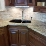 white and light brown groutless tiles in kitchen backsplash top and under kitchen cabinetry double sinks and single faucet luxurious granite countertop