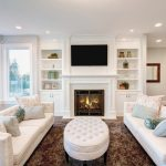 white built-in shelves and cabinets with electric fireplace building in the center small settee furniture in white comfortable sofas in white color brown fury carpet for living room