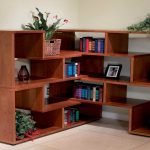 wide corner bookshelves unit in wood material  book arrangements some pictures with black frames  ceramic beige floor flowrer ornament