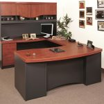 wood finishing top U shape desk with drawers and cabinets minimalits flat screen computer set several frames as wall decorations