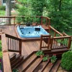 wood home patio with a large hot tub some pieces of patio furniture and beautiful decorative plants