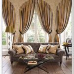 a window bay with arched windows installation  and gold-tone curtains  a dark-grey sofa with gold-colored pillows a glass panel table wood planks flooring