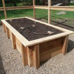 a wood box as high bed for planting which is surrounded by wire fence system