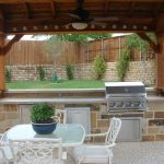 an outdoor kitchen set with simple white dining furniture and ceiling fan unit