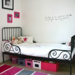 beautiful fury carpet with grey and pink color strips pattern a classic black metal bed furniture with white bedding some colorful boxes under the bed some pictures frames