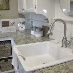 big porcelain farm sink with faucet  white marble kitchen countertop some containers for storing cooking supplies