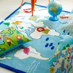 blue carpet for kids with ocean and islands theme a colorful pillow a globe with stand