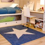 blue fury carpet with white star ornament in the center of carpet double-layered bedding with under storage a desk with under shelf and a white movable chair wood-finishing floor