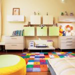 colorful carpet for kids with letter theme a comfy chair low study desk double white cabinets with floating boxes for storage a bed furnuiture with comfortable bedding