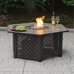 creative fire pit table in black with two glases of wine a wine bottle and a plate of fresh grape fruits