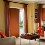 curtains and brown shades for sliding glass door a pair of chairs with beautiful patterns on seating feature a minimalist table with a pile of books and coffee jug