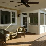 dark ceiling fan in porch a pair of outdoor cozy  arm chairs in rattan material and round rattan table with glass top wood planks floor on porch