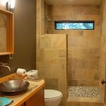 doorless showe room with small natural stone floors and brown ceramic wall system  simple vanity with wood surface and copper sink plus copper faucet a toilet appliance