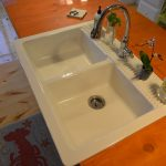 double farm sinks with stainless steel water faucet seen from top angle wood-finishing countertop for kitchen set