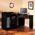 elegant corner desk in black with cabinet system and under shelf and also under sliding panel for putting the keyboard of computer a computer unit a scanner unit a round wall-clock a painting on the wall