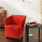 elegant red reading chair with black wood side-table with a pile of book collections metal tiny-stand lamp for reading unique-door wood buffet wood-finish flooring