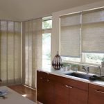 honeycomb window drapes for sliding glass door  a kitchen countertop with large square sink and faucet a kitchen island with seating