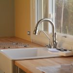 large and deep farm sink plus faucet a metal-wire for dishware stand brushed-wood kitchen countertop