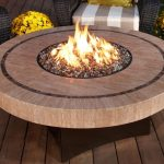 large round wood table with fire pit in the center  two beautiful flower arrangement on pots and two black rattan chairs with strips patterns setaing feature