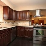 several rubbed bronze kitchen appliances in elegant kitchen room  dark wood planks floors dark wood finish kitchen cabinetry