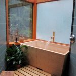 simple and small bathroom remodel with dominant wood material a corner wood tub soaking  wood planks walkway a small and low wood shower bench black natural tiles for floors