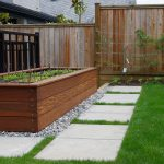 single wood box concrete planter in home garden a walk-ways made from natural stones wood lattice fence for outdoor area well-maintain grass in the home garden
