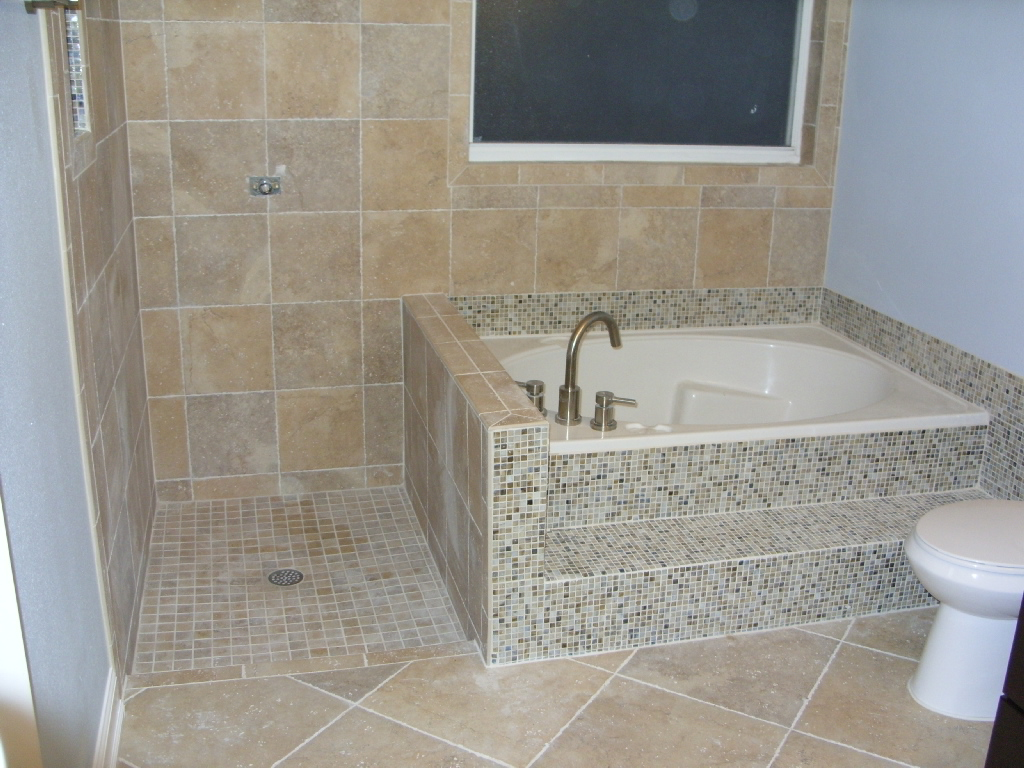 small and deep tub with water sprayer and mosaic tub-walls a closet unit  small ceramic tiles for shower floors large brown ceramic tiles for bathroom floors