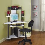 small corner desk for computer with top shelving units for audio systems and sliding panel for keyboard  a movable black chair two flower paintings for wall decoration hardwood floors